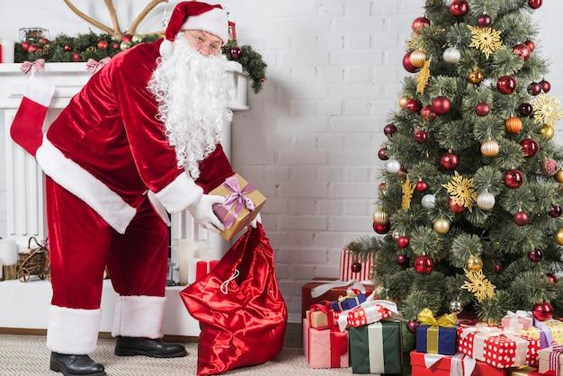 Père Noël Mettant Des Cadeaux Sous Un Arbre De Noël Photo gratuit