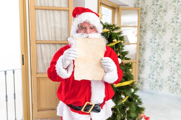 Père noël montrant une lettre vide Photo gratuit