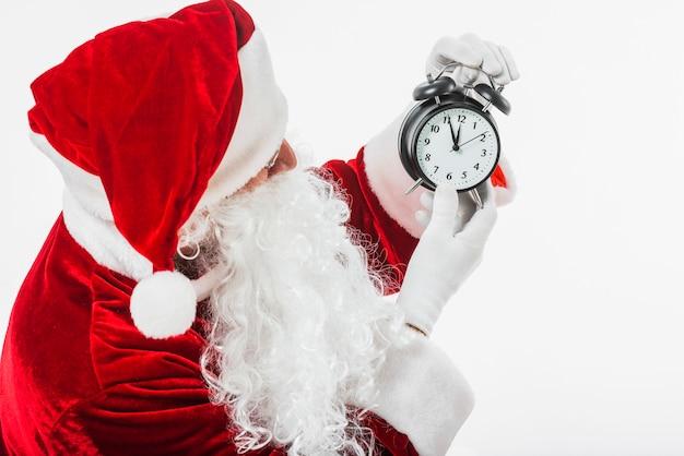 Père noël regarde l'horloge dans les mains Photo gratuit