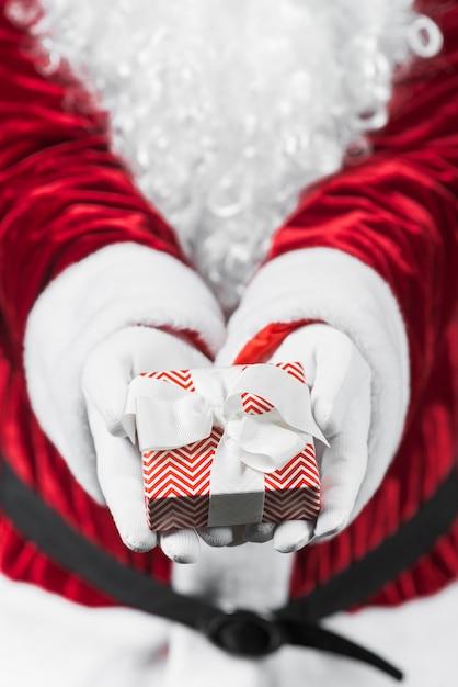 Père noël en rouge tenant petite boîte-cadeau dans les mains Photo gratuit