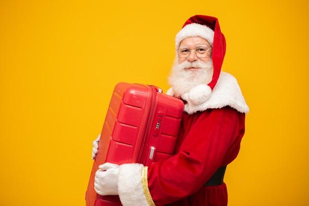 Père noël avec sa valise. concept de voyage du nouvel an Photo Premium