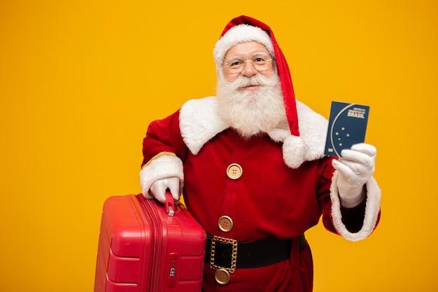 Père noël avec sa valise. détenir un passeport brésilien. concept de voyage du nouvel an Photo Premium