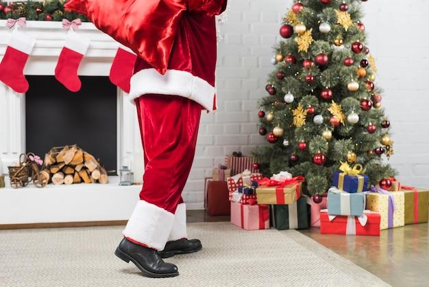 Père noël avec sac de cadeaux derrière le dos allant à l'arbre de noël Photo gratuit