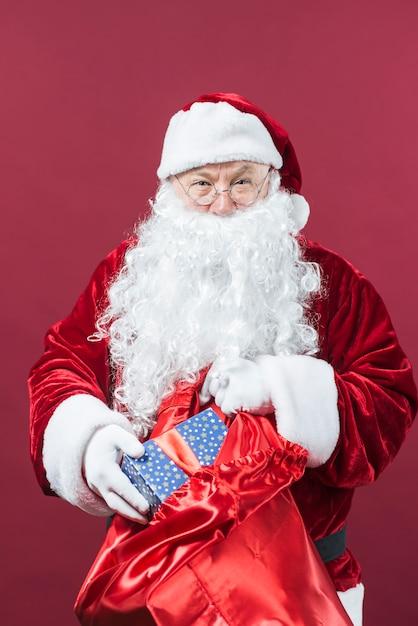 Père noël se fait une boîte-cadeau dans un grand sac Photo gratuit
