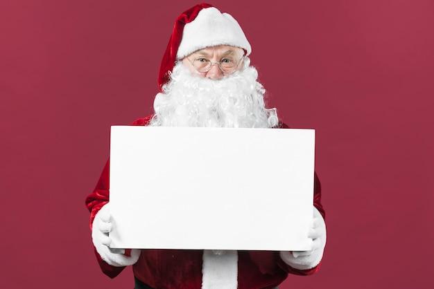 Père noël tenant du papier blanc dans les mains Photo gratuit
