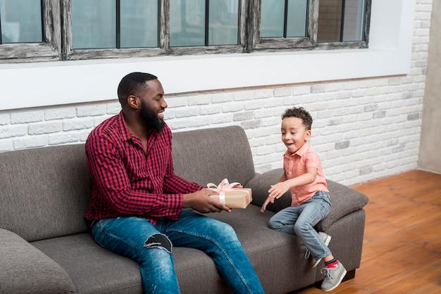 Père noir, cadeau cadeau, à, émerveillé, fils Photo gratuit