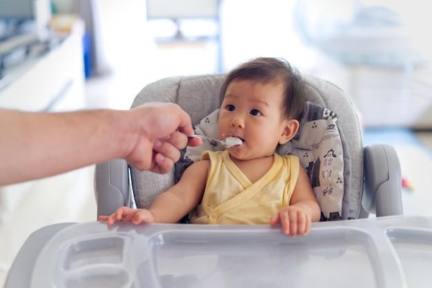Père nourrir la bouillie à son enfant sur le siège de nourrisson. Photo Premium