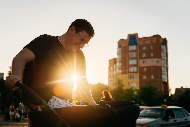 Père papa avec poussette landau nouveau-né à l'extérieur pendant le coucher du soleil Photo Premium