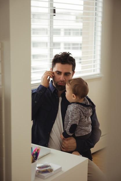 Père Parlant Au Téléphone Mobile Tout En Tenant Son Bébé Photo gratuit