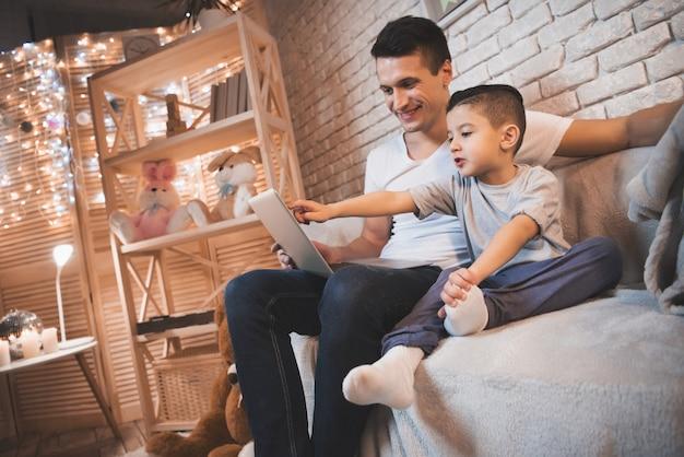 Père et petit fils regardent un film sur un ordinateur portable. Photo Premium