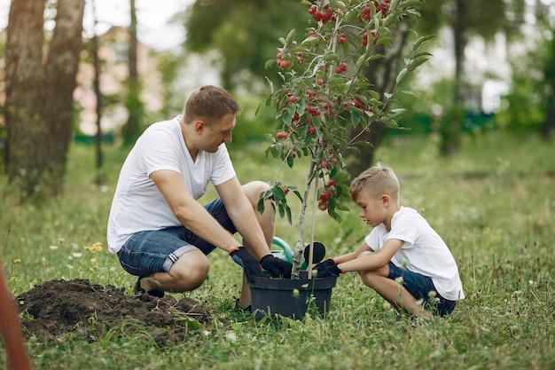 Père Avec Petit Fils Sont En Train De Planter Un Arbre Sur Une Cour Photo gratuit