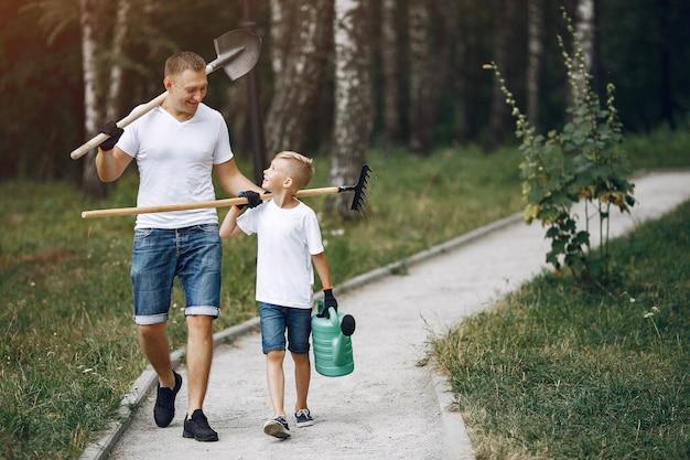 Père avec petit fils sont en train de planter un arbre dans un parc Photo gratuit