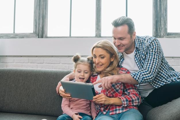Père pointant sur tablette numérique avec sa femme souriante et sa fille à la maison Photo gratuit