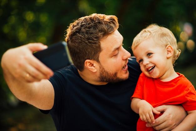 Père prenant un selfie et regardant son enfant Photo gratuit