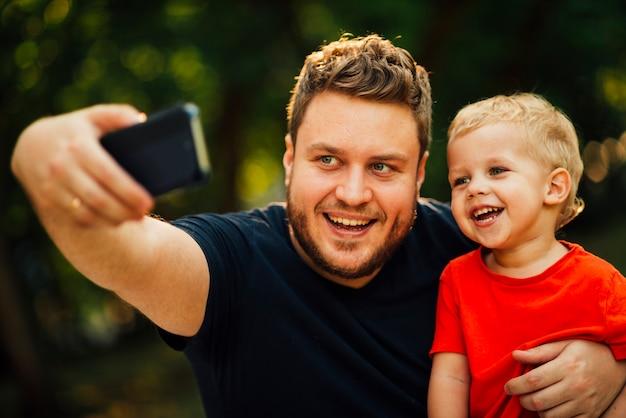 Père prenant un selfie avec son fils Photo gratuit