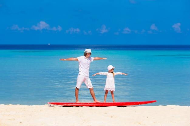 Père avec sa petite fille à la plage, pratiquant la position de surf Photo Premium
