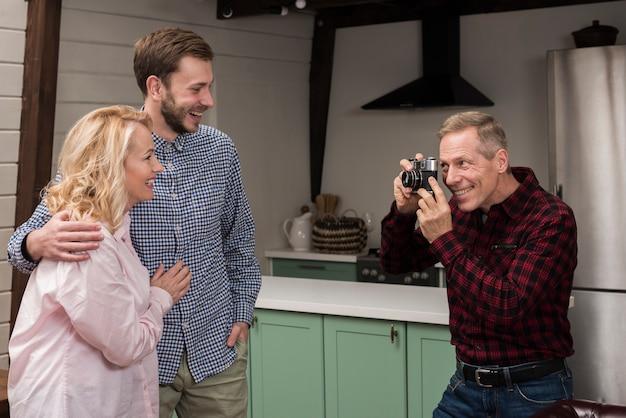 Père Smiley Prenant Une Photo De Maman Et Son Fils Dans La Cuisine Photo gratuit