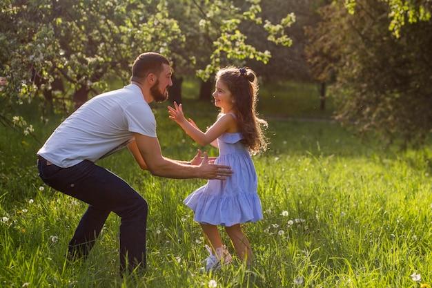 Père soulevant sa fille dans le parc Photo gratuit