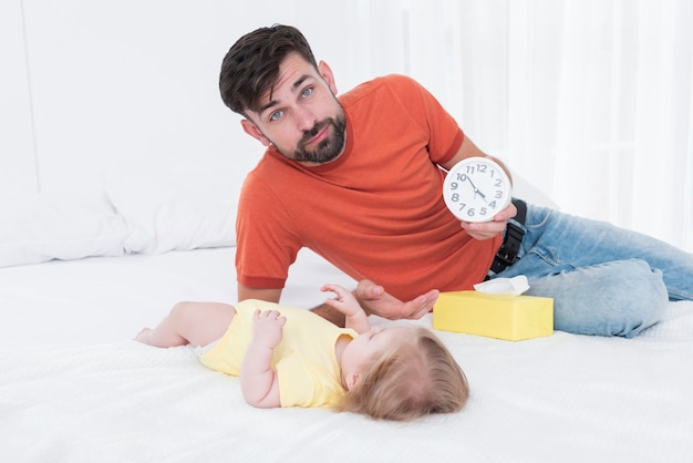 Père tenant une horloge à côté de bébé au lit Photo gratuit