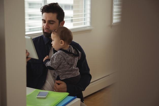 Père Tenant Son Bébé Tout En Utilisant Une Tablette Numérique Au Bureau Photo gratuit