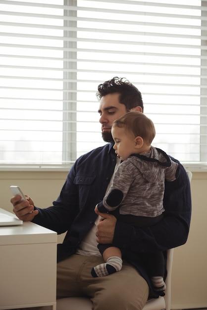 Père Tenant Son Bébé Tout En Utilisant Un Téléphone Mobile Au Bureau Photo gratuit