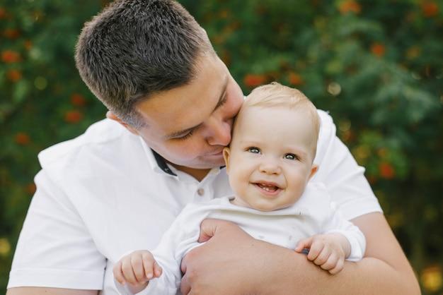 Un Père Tient Son Petit Fils Dans Ses Bras Et L'embrasse. Le Bébé Est Souriant Et Heureux. Fête Des Pères Photo Premium