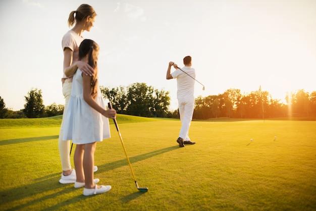 Père tire au golf heureuse famille de joueurs. Photo Premium