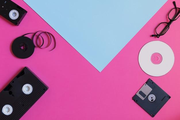 Périphériques De Stockage Rétro: Deux Vidéocassettes, Une Disquette, Un Cd Et Des Lunettes. Concept Technologique Obsolète Sur Fond De Papier De Couleur Bleu Rose Photo Premium