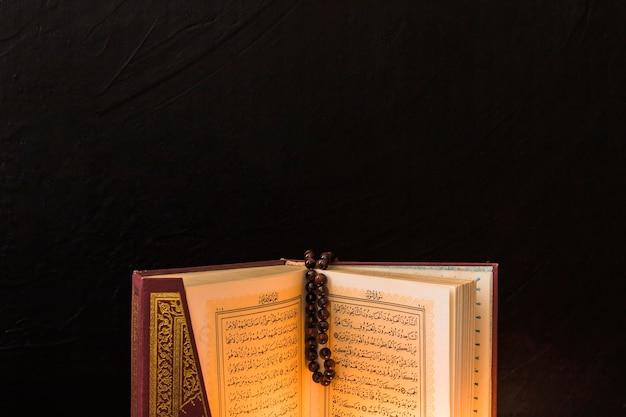Perle de prière sur un livre musulman ouvert Photo gratuit