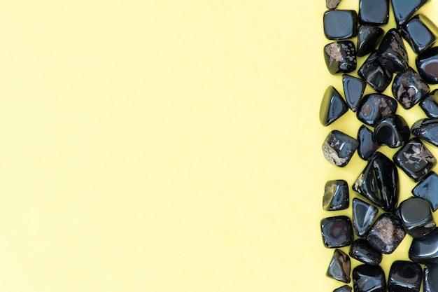 Perles, perles noires sur une vue de dessus d'un fond blanc jaune Photo Premium