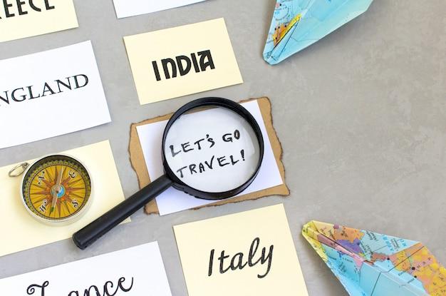 Permet de voyager mots de texte, sélection du pays, carte loupe boussole, fond gris Photo Premium