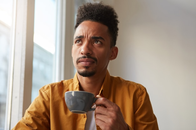 Perplexe Homme Afro-américain Porte Une Chemise Jaune, Assis à Table Dans Un Café Et Boit Du Café, Se Souvient Si Le Fer S'est éteint Avant De Quitter L'appartement. Regardant Pensivement Au Loin. Photo gratuit