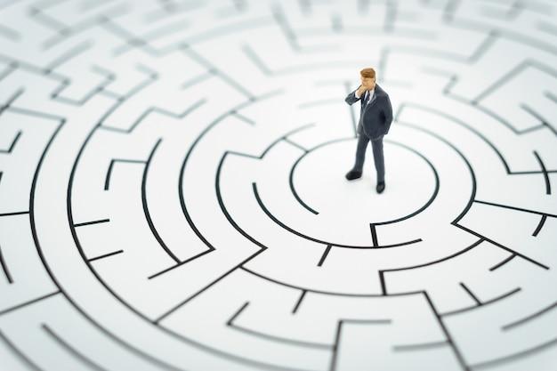 Personnage miniature homme d'affaires marcher dans un labyrinthe. Photo Premium