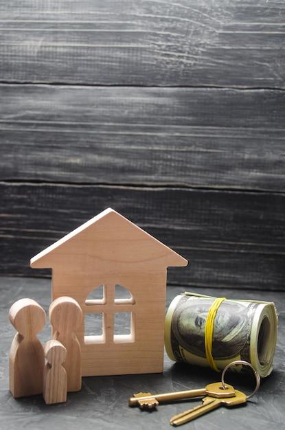 Les personnages en bois de la famille se tiennent près d'une maison en bois, des clés. Photo Premium