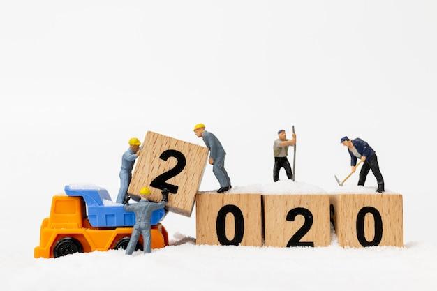 Personnages miniatures, une équipe de travailleurs crée un bloc de bois numéro 2020 Photo Premium