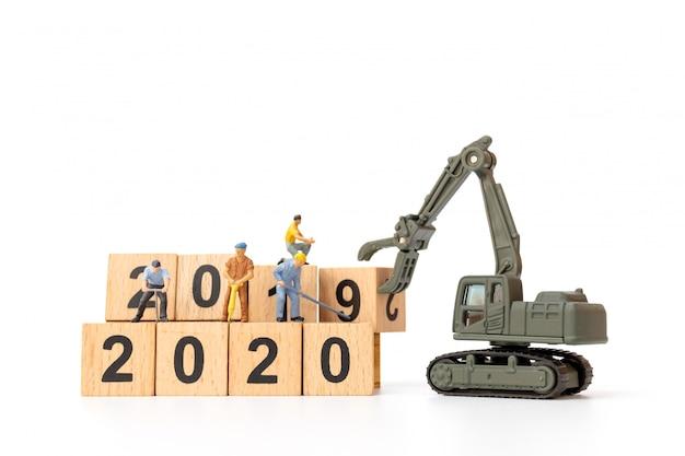 Personnages miniatures: une équipe de travailleurs crée un bloc de bois numéro 2020 Photo Premium