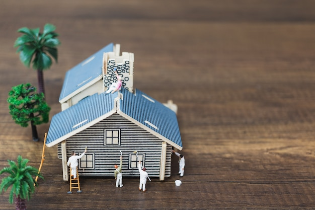Personnages miniatures: équipe de travailleurs en train de peindre une nouvelle maison. Photo Premium