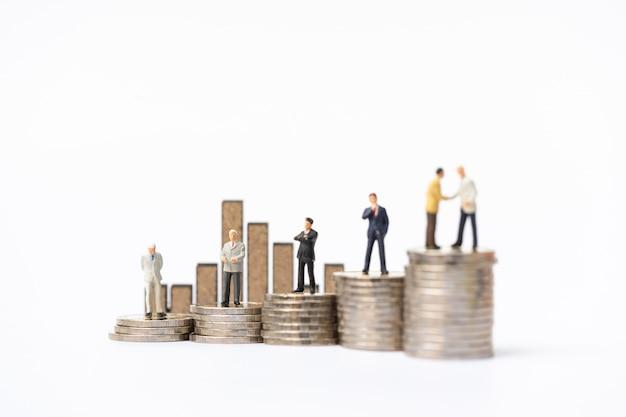 Personnages miniatures: groupe d'hommes d'affaires debout sur la pile de pièces de monnaie avec le panneau à barres en bois en toile de fond Photo Premium