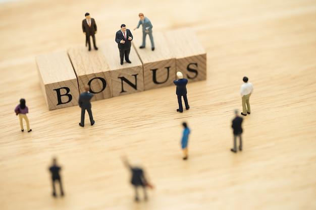Personnages miniatures hommes d'affaires en attente de gains bénéfices de l'entreprise Photo Premium