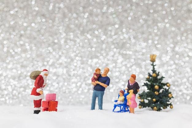 Personnages Miniatures: Père Noël Et Enfants Sur Fond De Neige Photo Premium