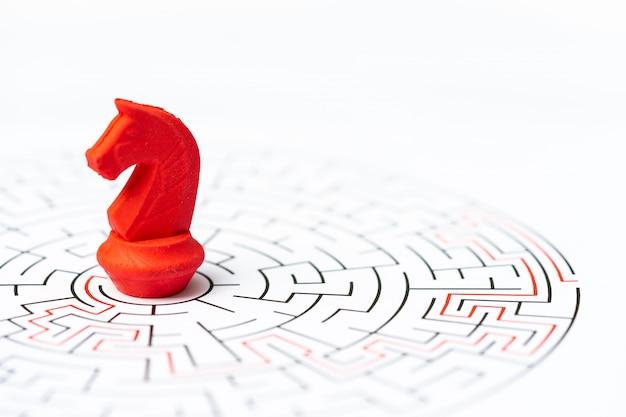Personnages miniatures, pièce d'échecs knight dans le labyrinthe ou le labyrinthe. Photo Premium