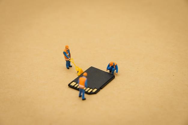 Personnages miniatures réparation de travailleur de la construction avec une carte de stockage ou une carte mémoire Photo Premium