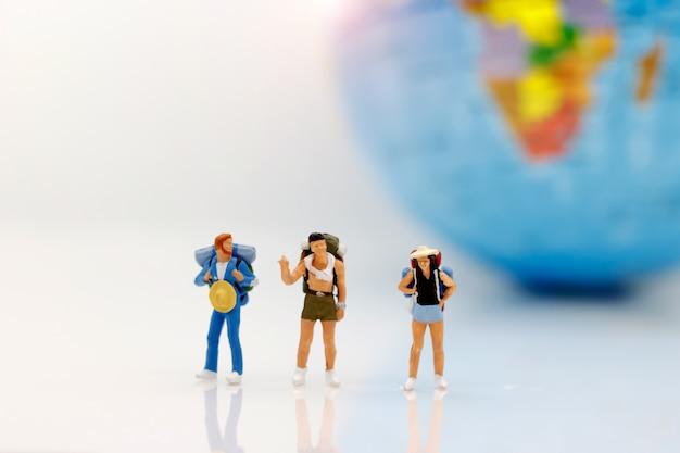 Personnages miniatures, routards avec globe marchant à destination. Photo Premium