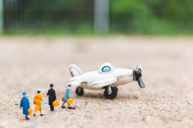 Personnages miniatures: des voyageurs munis de bagages de cabine montent dans l'avion Photo Premium