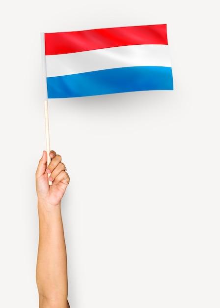 Personne agitant le drapeau du grand-duché de luxembourg Photo gratuit