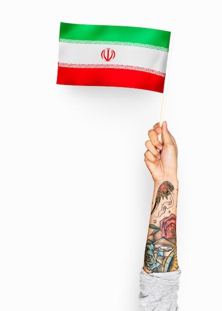 Personne agitant le drapeau de la république islamique d'iran Photo gratuit