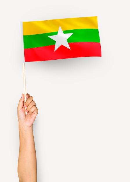 Personne agitant le drapeau de la république de l'union du myanmar Photo gratuit