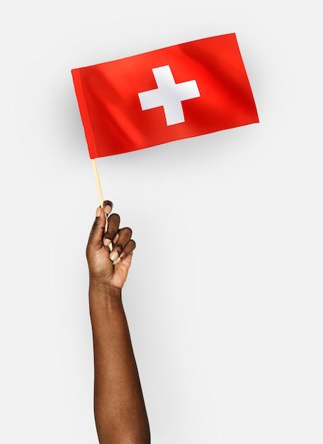 Personne agitant le drapeau de la suisse Photo gratuit