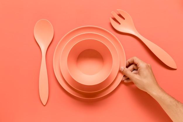 Personne anonyme mettant la vaisselle rose sur la table Photo gratuit