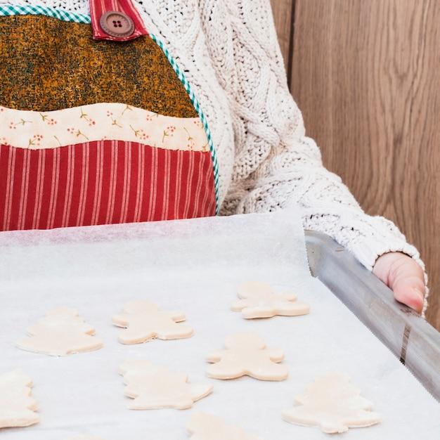 Personne apportant une plaque à pâtisserie avec des biscuits de noël Photo gratuit